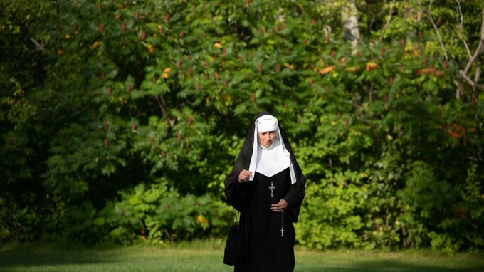nun-walking-near-trees-2447958