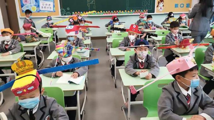 Čínští školáci v kloboucích s metrovými tyčemi