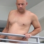 Vin Diesel shows off his giant biceps and unusually round tummy as he hangs out on his hotel balcony in Miami