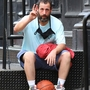 Adam Sandler holds a basketball and sits down to rest  after a game in NYC